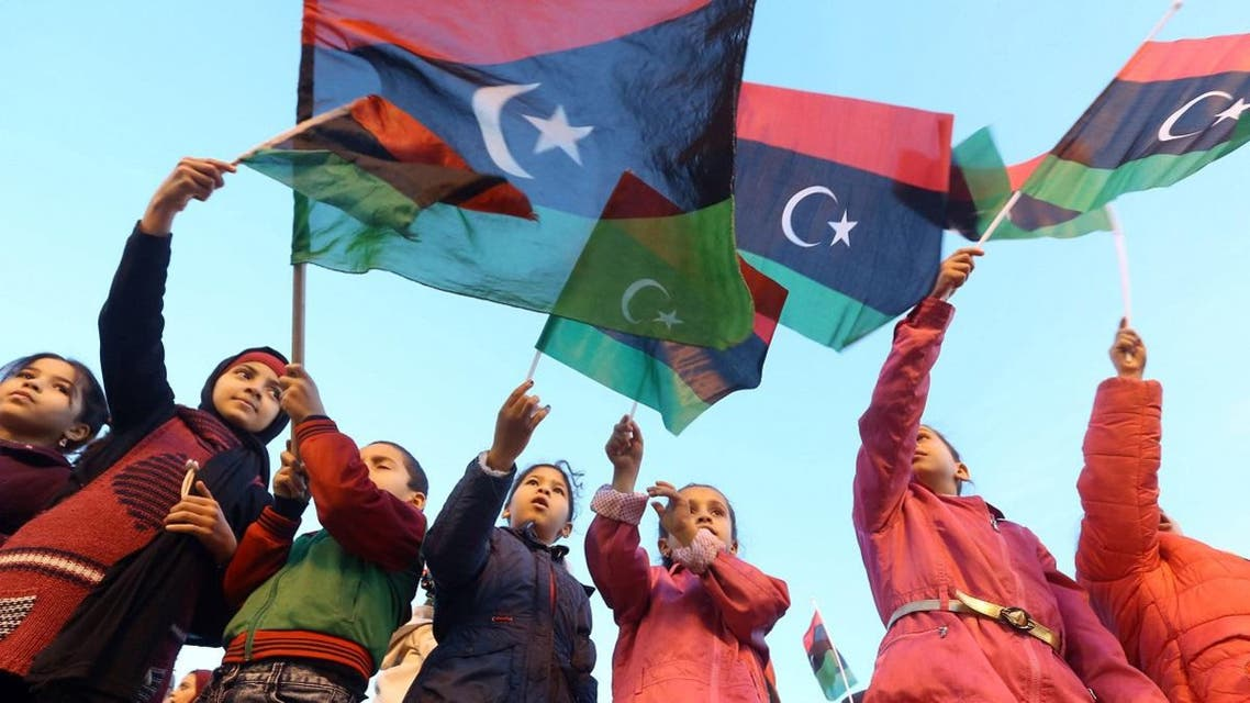 Libyan children wave their country's national flags as they celebrate in Tripoli's Martyrs' Square on February 16, 2018. (AFP)