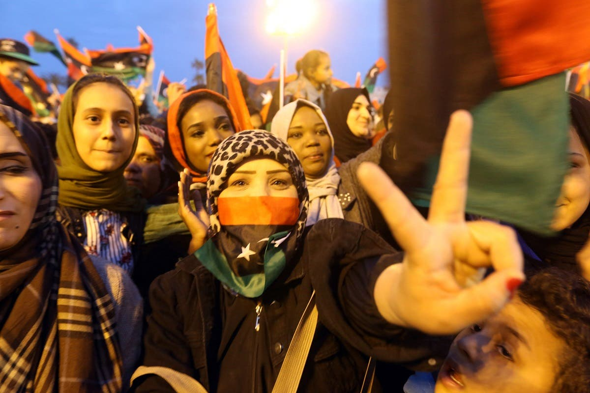 A Libyan woman flashes the victory gesture while others wave national flags as they attend a celebration marking the seventh anniversary of the Libyan revolution. (AFP)