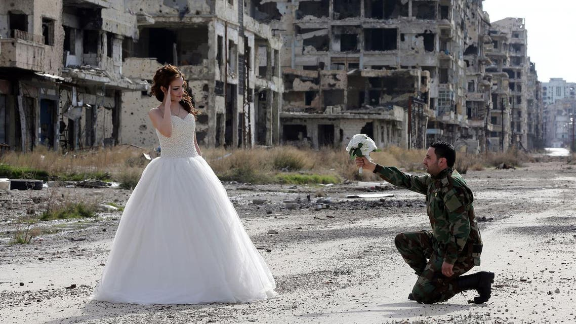 Newlywed Syrian couple, Nada Merhi, 18, and Syrian army soldier Hassan Youssef, 27, pose for a wedding picture amid heavily damaged buildings in the war-ravaged city of Homs, Syria, on February 5, 2016. (AFP)
