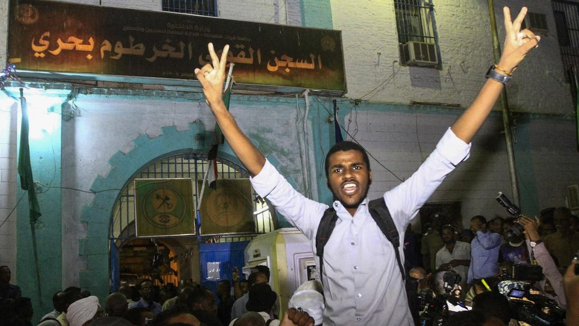 Family members shout slogans as they wait outside the Kobar prison in north Khartoum to welcome their loved ones. (AFP)