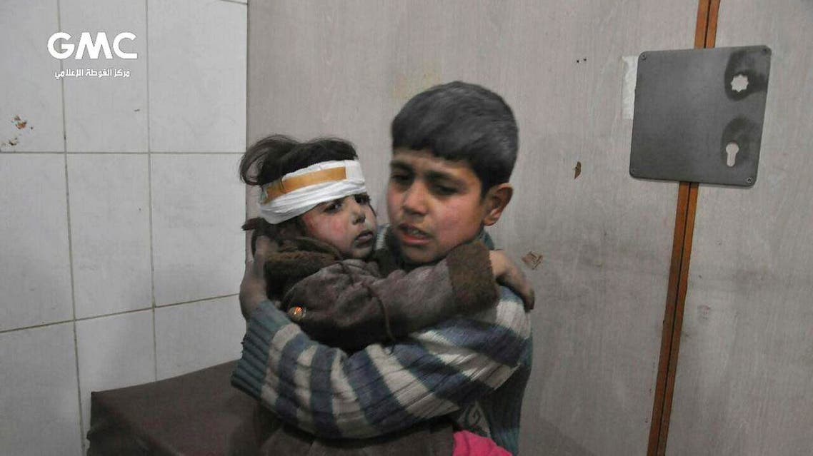 Two Syrian kids who were wounded during airstrikes and shelling by Syrian government forces, sit at a makeshift hospital in Ghouta. (AP)