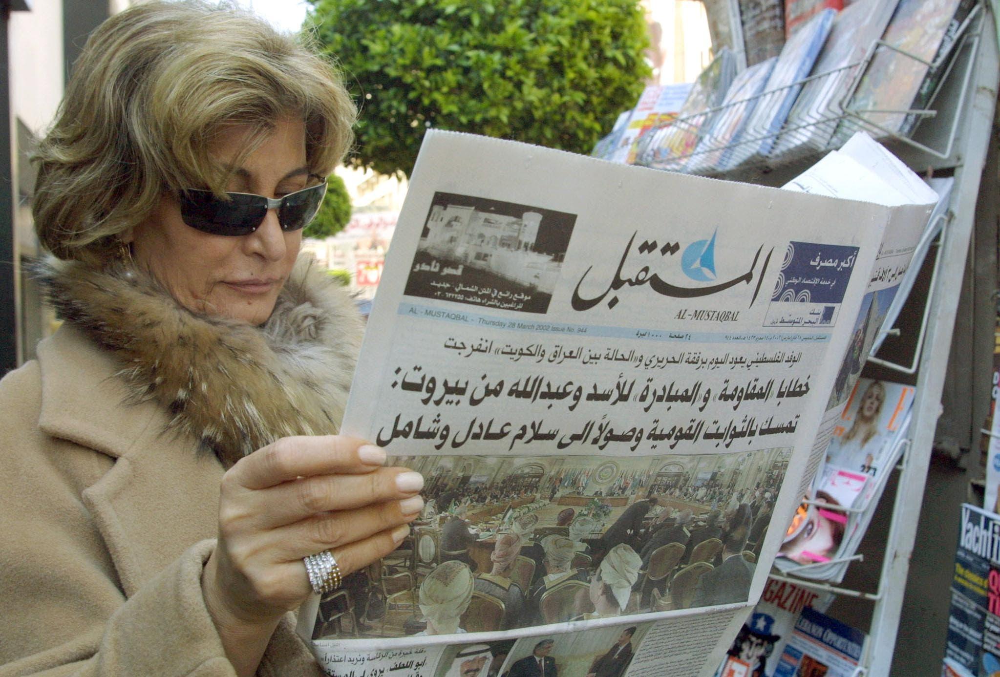 لبنانية تقرأ صحيفة عقب القمة العربية في بيروت 2002
