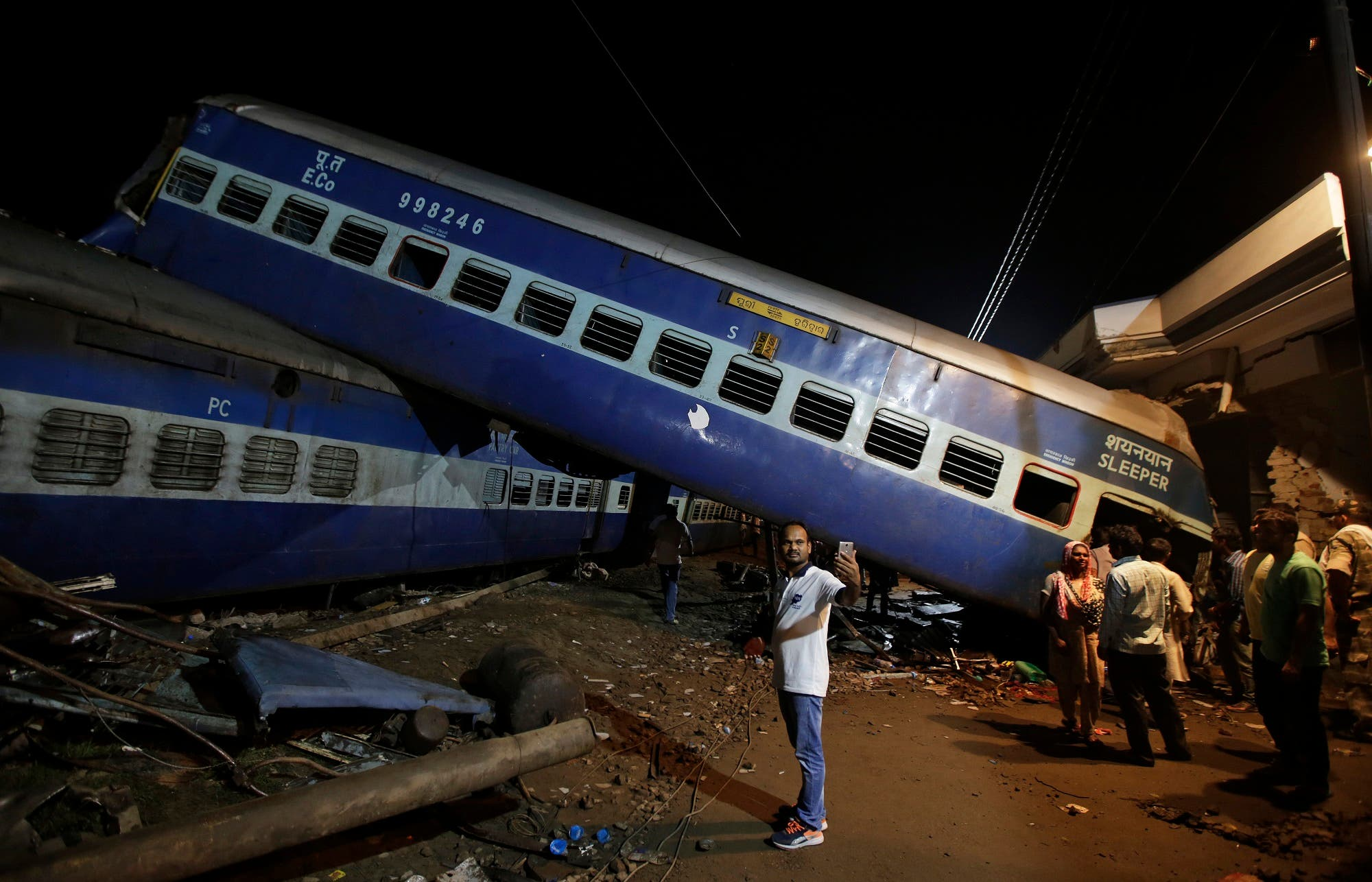 A man takes a selfie near the upturned coaches of a train after an accident in Uttar Pradesh on Aug. 20, 2017. (AP)