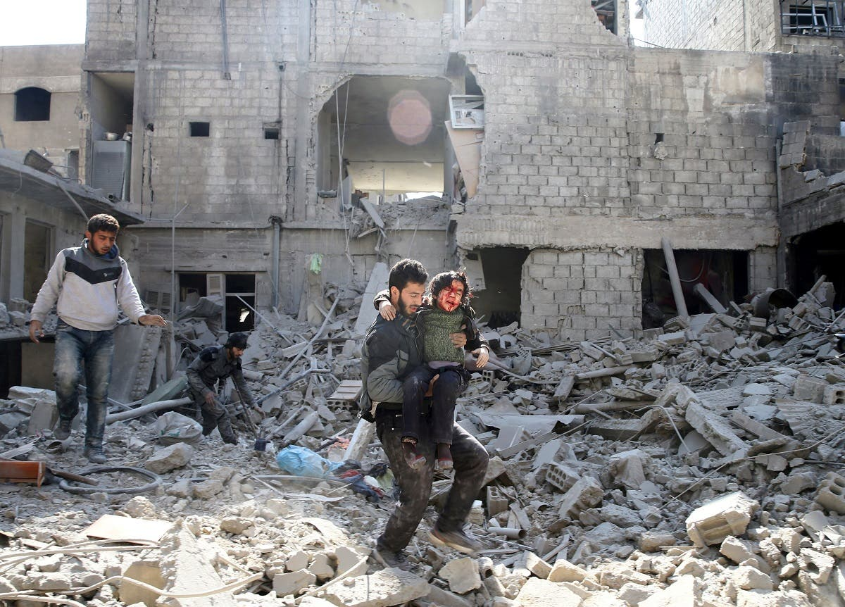 A man carries an injured boy as he walks on rubble of damaged buildings in the rebel held besieged town of Hamouriyeh. (Reuters)
