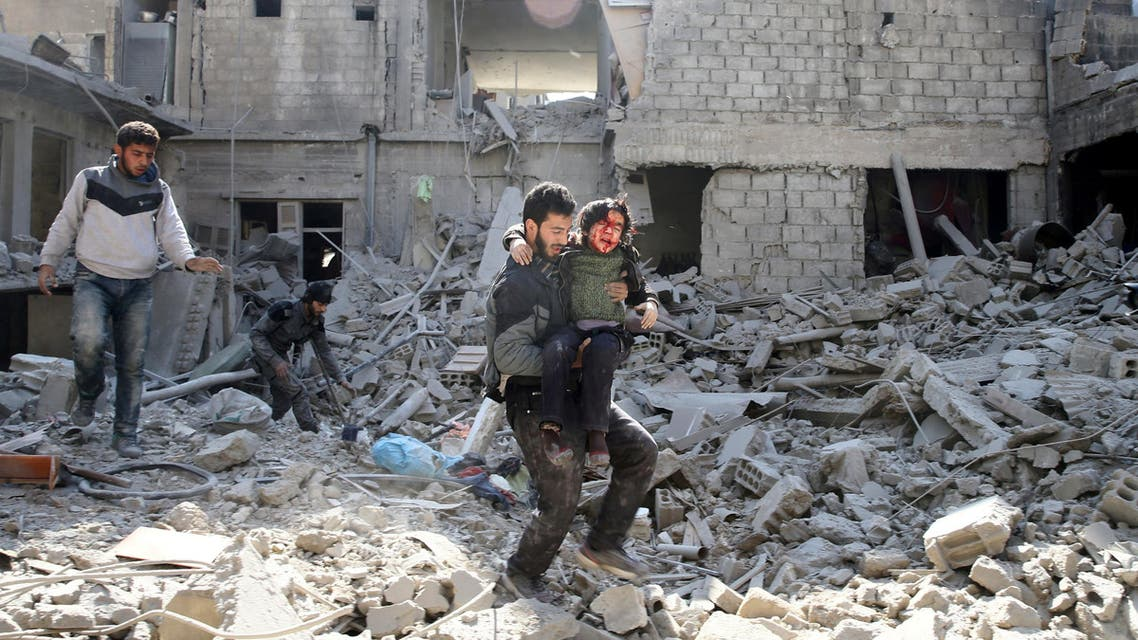 ATTENTION EDITORS - VISUAL COVERAGE OF SCENES OF INJURY OR DEATH A man carries an injured boy as he walks on rubble of damaged buildings in the rebel held besieged town of Hamouriyeh, eastern Ghouta, near Damascus, Syria February 21, 2018. REUTERS/Bassam Khabieh TEMPLATE OUT TPX IMAGES OF THE DAY