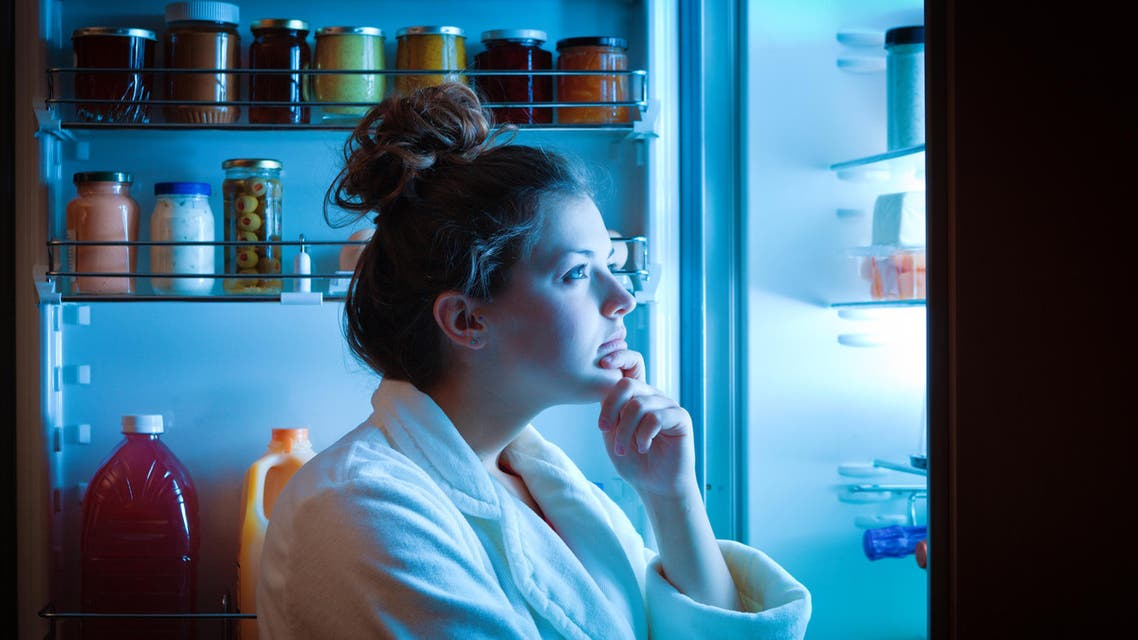 Dieting Young Woman Late Night Making Choices on What to Eat - Stock image...