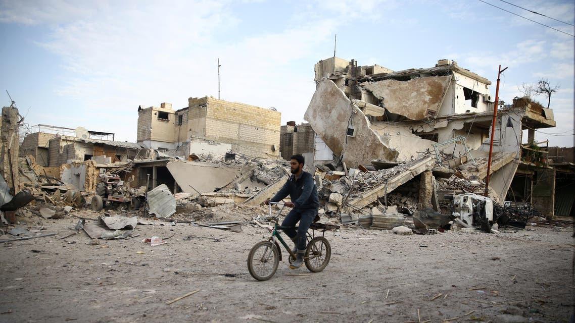 شاب يركب دراجة هوائية بالقرب من منازل مدمرة في دوما بالغوطة الشرقية 33.