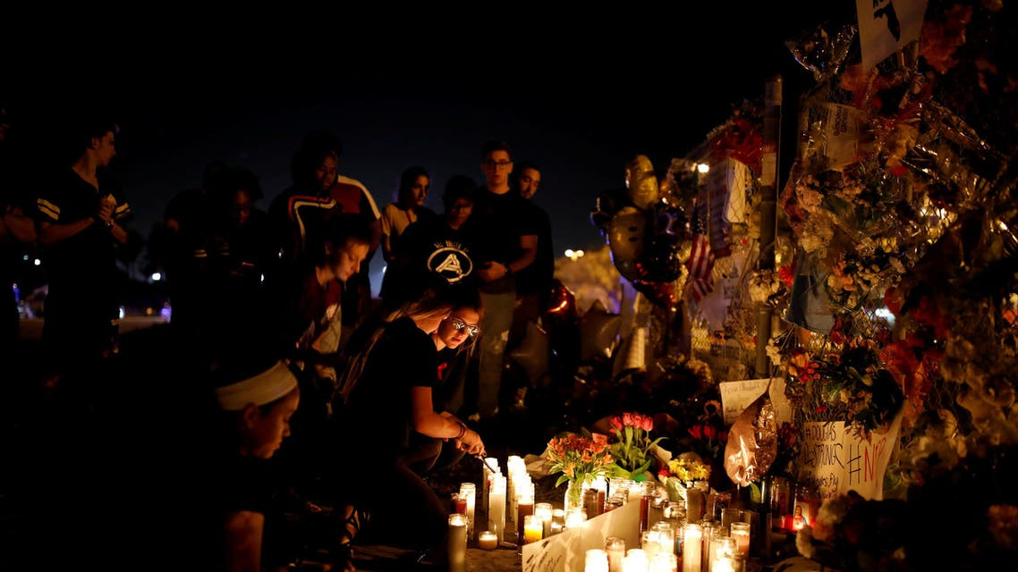 People light candles in front of mementoes placed in front of the fence of the Marjory Stoneman Douglas High School to commemorate the victims of the mass shooting, in Parkland, Florida, U.S., February 21, 2018. REUTERS/Carlos Garcia Rawlins TPX IMAGES OF THE DAY