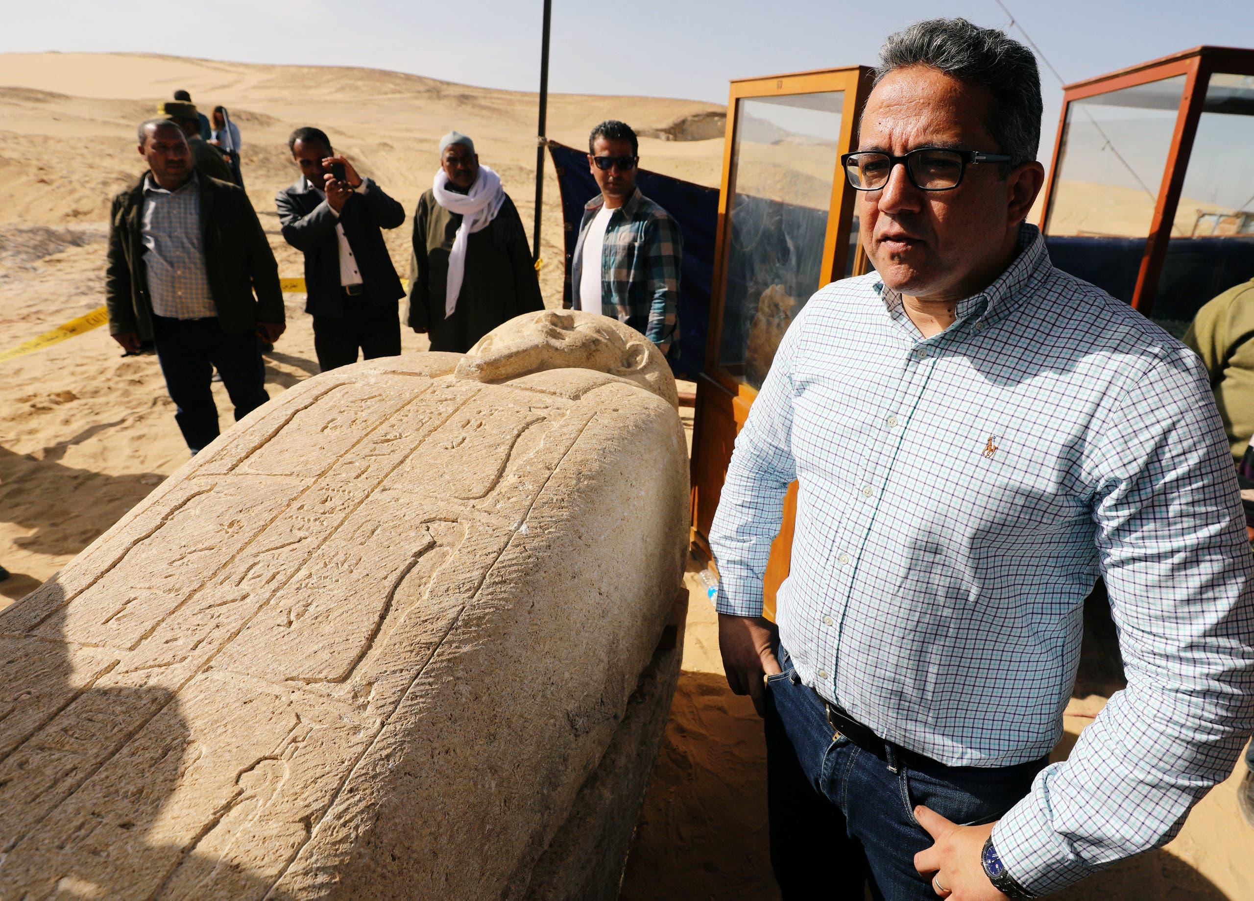 وزير الآثار المصري خالد العناني بجانب أحد التماثيل المكتشفة