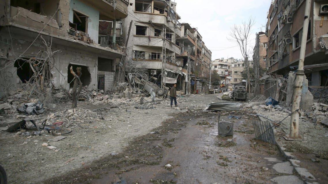 أشخاص يسيرون بين المباني المدمرة بعد غارة جوية في مدينة دوما في الغوطة 33
