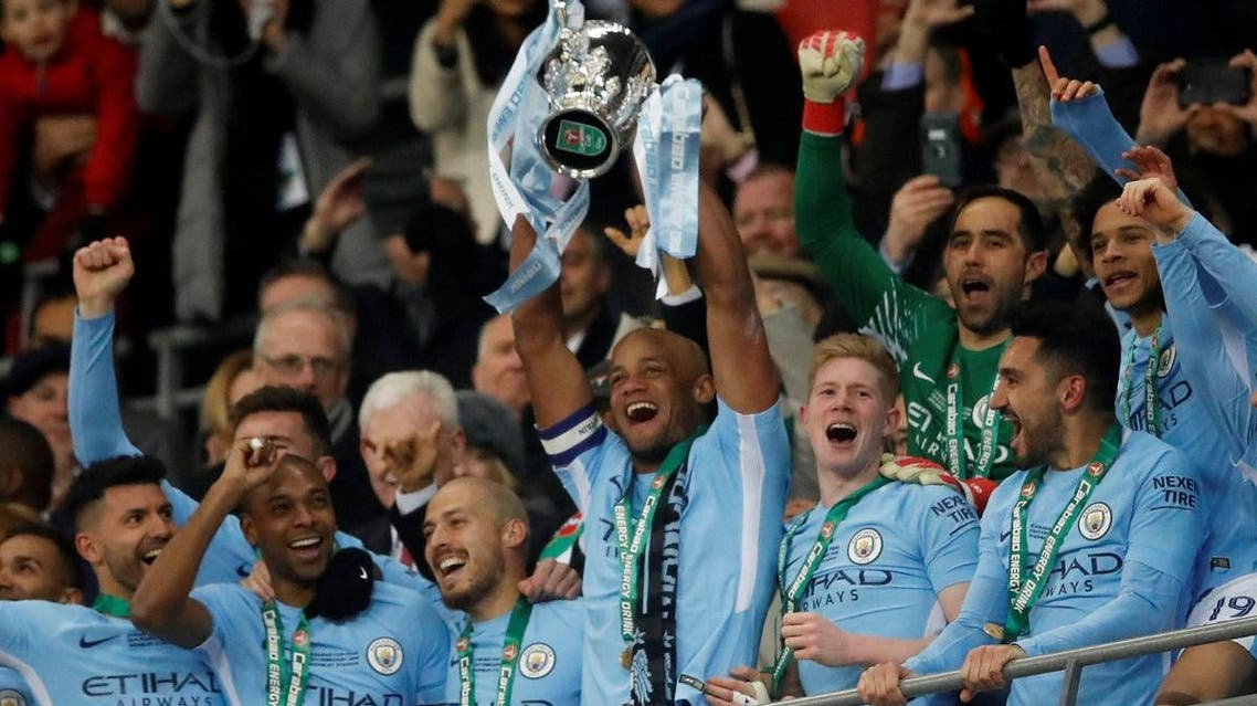 Manchester City's Vincent Kompany lifts the trophy as they celebrate winning the Carabao Cup. (Reuters)
