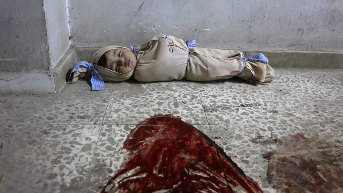 The body of a Syrian baby lies wrapped in a shroud on the floor of a makeshift clinic following Syrian government bombardments in Douma, in the besieged Eastern Ghouta region on the outskirts of the capital Damascus on February 22, 2018. (AFP)