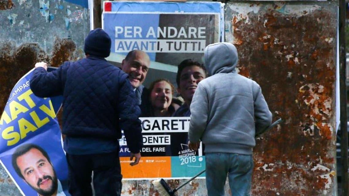 رجلان يعلقان ملصقات انتخابية في روما