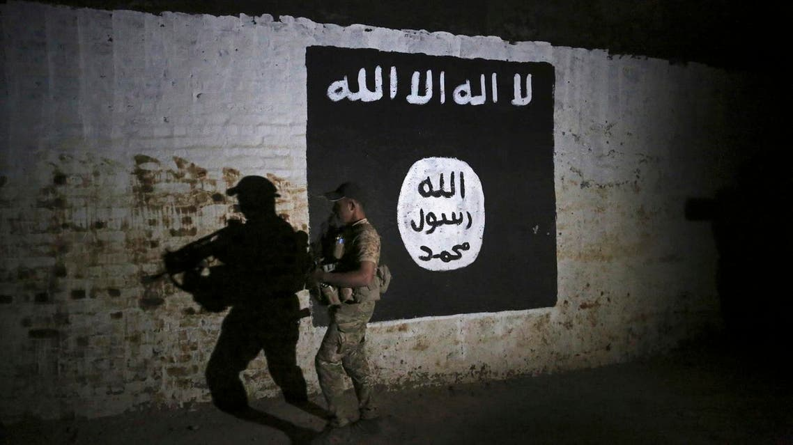An Iraqi soldier inspects a recently-discovered train tunnel, adorned with an ISIS group flag. (File photo: AP)