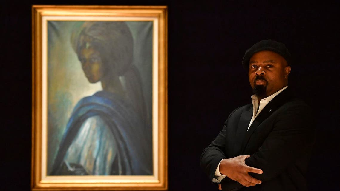 Nigerian author Ben Okri poses with a work of art by Nigerian painter and sculptor Ben Enwonwu entitled 'Tutu' at auction in Bonhams auction house London on February 7, (AFP)