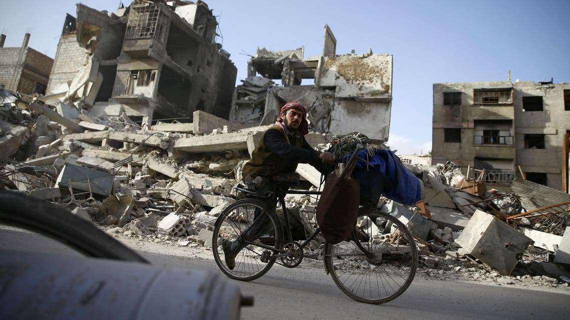 A handicapped man rides a bicycle past damaged buildings in the besieged town of Douma in eastern Ghouta in Damascus, Syria, March 1, 2018. REUTERS/Bassam Khabieh