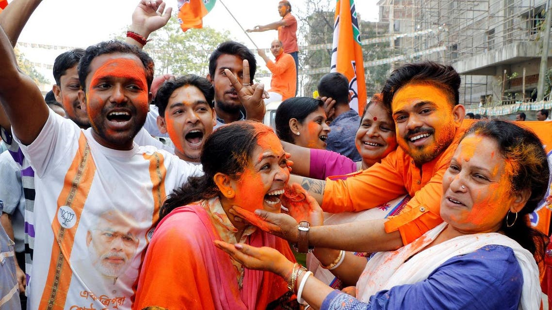 A supporter of India's ruling Bharatiya Janata Party (BJP) reacts as others apply color powder on her face while they celebrate after learning of the initial poll results of Tripura state assembly elections, in Agartala, India, on March 3, 2018. (Reuters)
