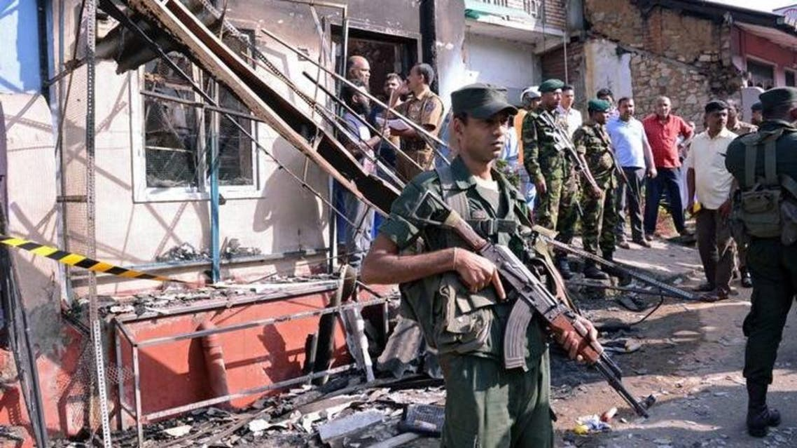 جنود من جيش سريلانكا قرب منزل محترق بعد اشتباكات في منطقة كاندي بوسط البلاد يوم الثلاثاء