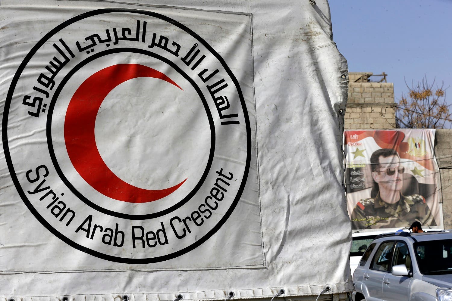 Syrian Arab Red Crescent vehicles carrying aid wait at a checkpoint on the outskirts of Damascus before delivering aid to the rebel-held enclave on March 5, 2018. (AFP)