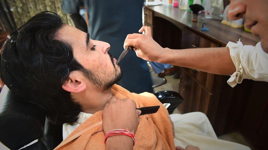 A Pakistani hairdresser styles the beard of a customer at a hair salon in Peshawar. (AFP)