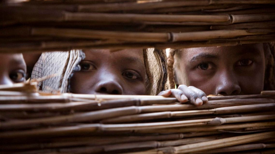 Refugees who fled the conflict in Sudan's western Darfur region peek through a hole in a shelter to watch a circumcision ceremony at Djabal camp near Gos Beida in eastern Chad June 19, 2008. (Reuters)