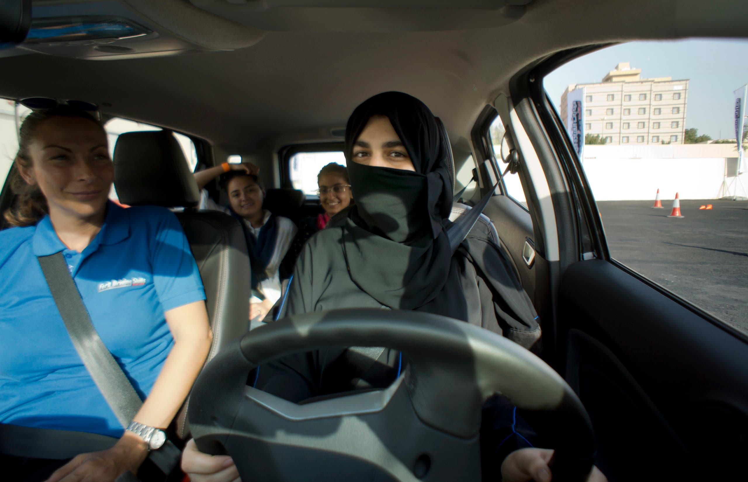 Razan, right, sits for the first time in the driver's seat, with her trainer Francesca Pardini, an Italian ex-race car driver, during training sponsored by Ford Motor, in Jiddah, Saudi Arabia, Tuesday, March 6, 2018. (AP