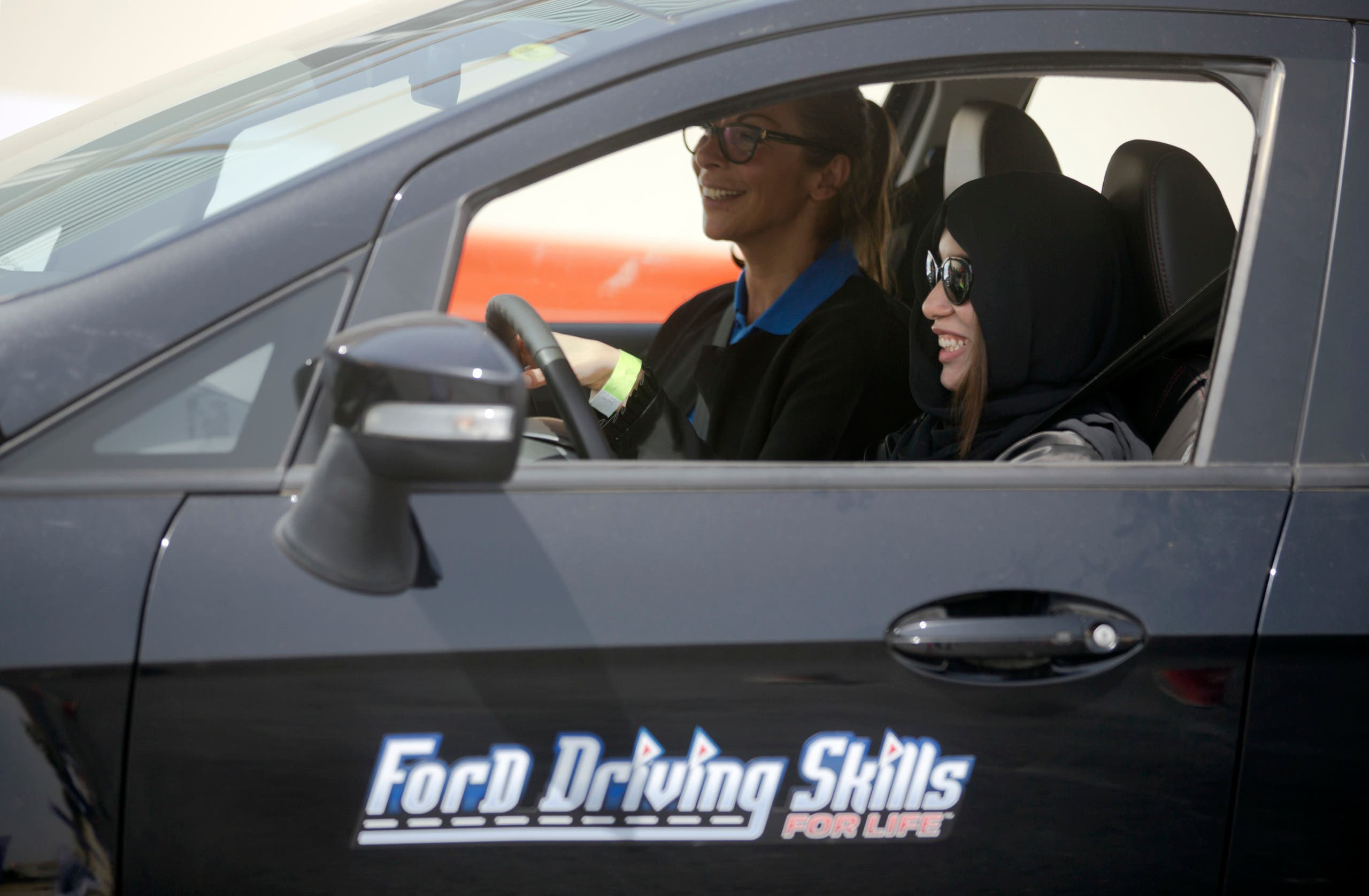 Fatima Salem, right, giggles as she sits for the first time in the driver's seat, with her trainer Francesca Pardini, an Italian ex-race car driver, during training sponsored by Ford Motor, in Jiddah, Saudi Arabia, Tuesday, March 6, 2018. (AP)