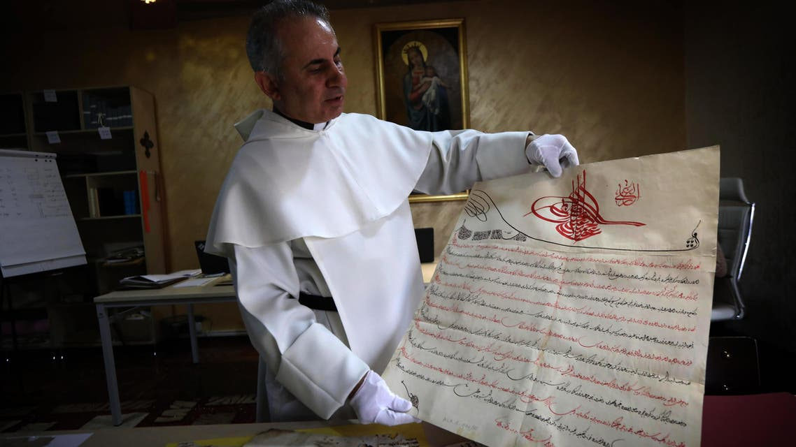 6)Father Najeeb Michaeel displays a manuscript at the Oriental Manuscript Digitisation Centre (CNDO) in Arbil, the capital of Iraq's autonomous northern Kurdish region, on March 1, 2018. (AFP)