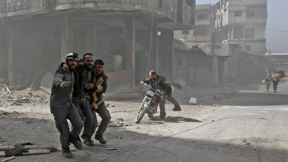 Volunteers from the Syrian civil defence help a man in Hamouria during Syrian government shelling on rebel-held areas in the Eastern Ghouta region on the outskirts of the capital Damascus on March 6, 2018. Heavy air strikes and clashes shook the Syrian rebel enclave of Eastern Ghouta, as France and Britain called for an emergency UN Security Council meeting on the escalating violence. ABDULMONAM EASSA / AFP