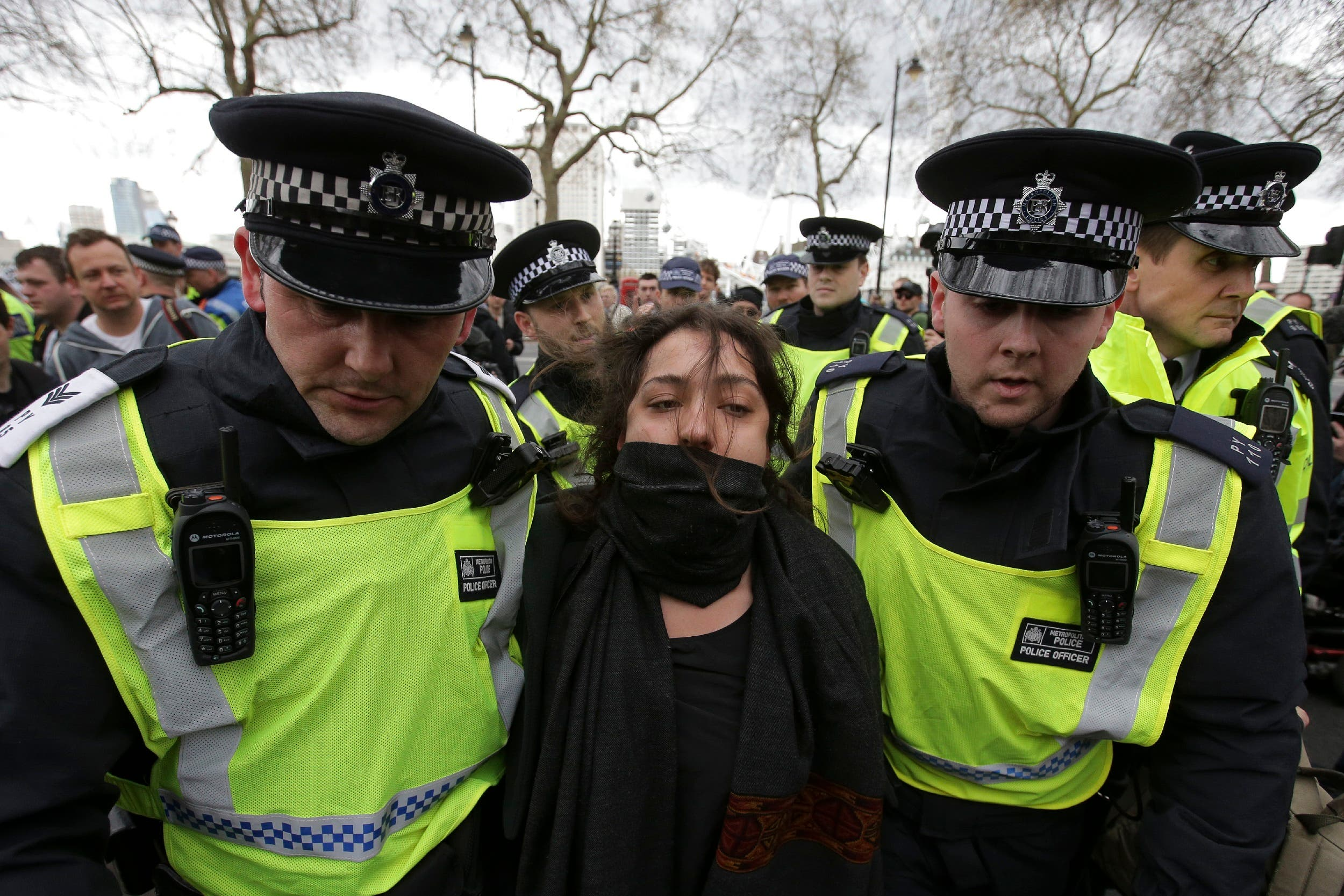 An activist from a counter demonstration organized by the Unite Against Fascism against the marches by the far-right groups Britain First and the English Defense League (EDL) is detained by police in central London on April 1, 2017. (AFP)
