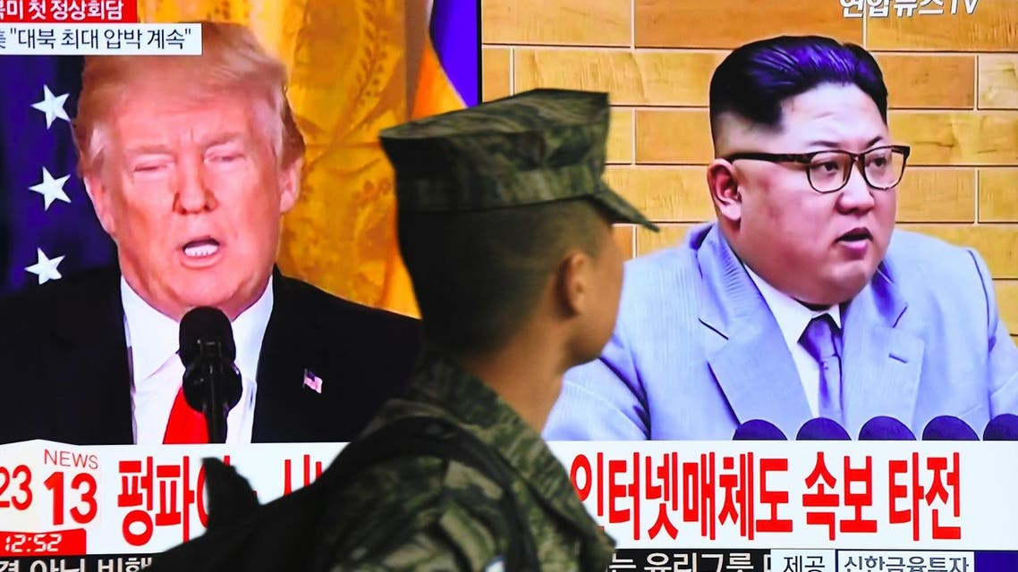A South Korean soldier walks past a TV screen showing pictures of US President Donald Trump (L) and North Korean leader Kim Jong Un at a railway station in Seoul on March 9, 2018.  (AFP)