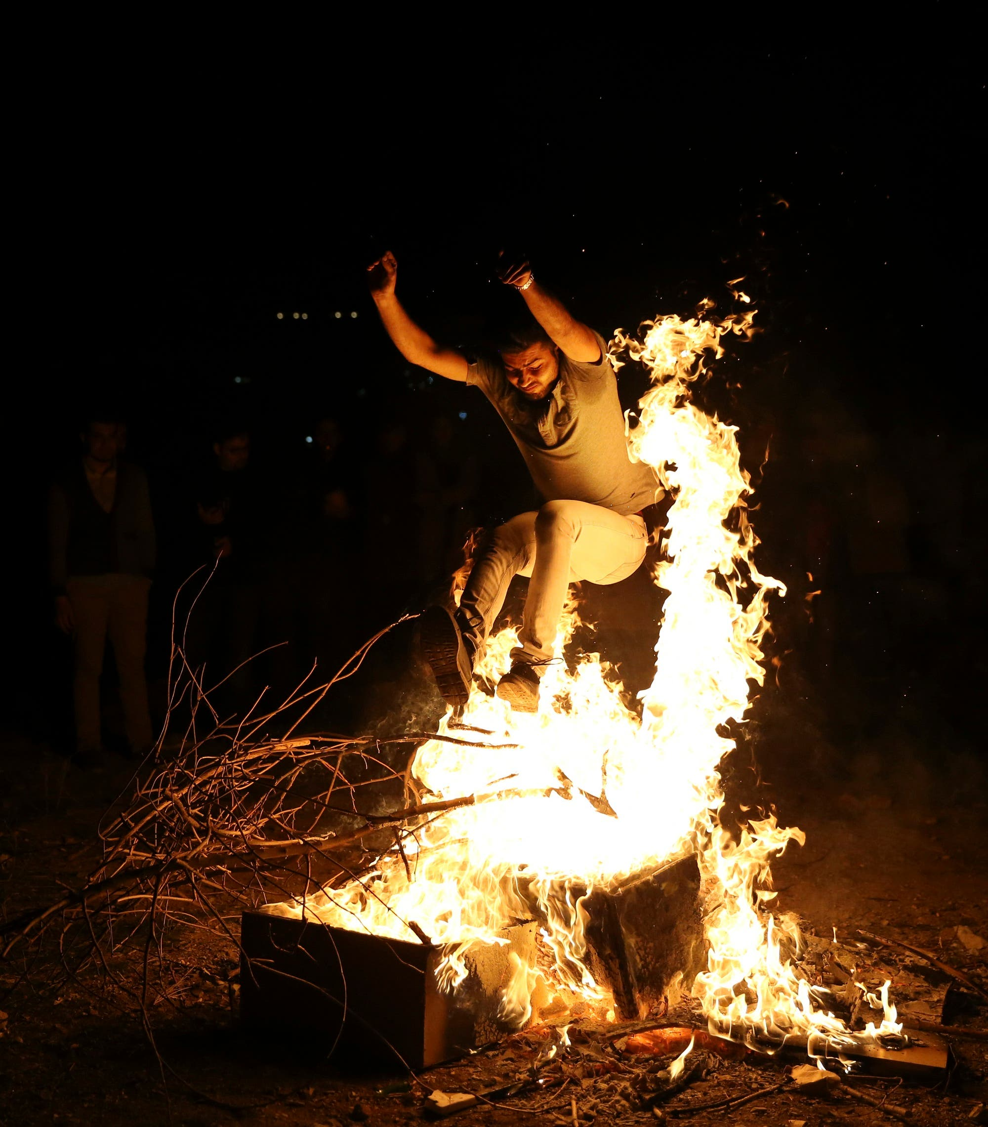 An Iranian man jumps over a bonfire during Chaharshanbe Souri in Tehran on March 17, 2015. (AP)