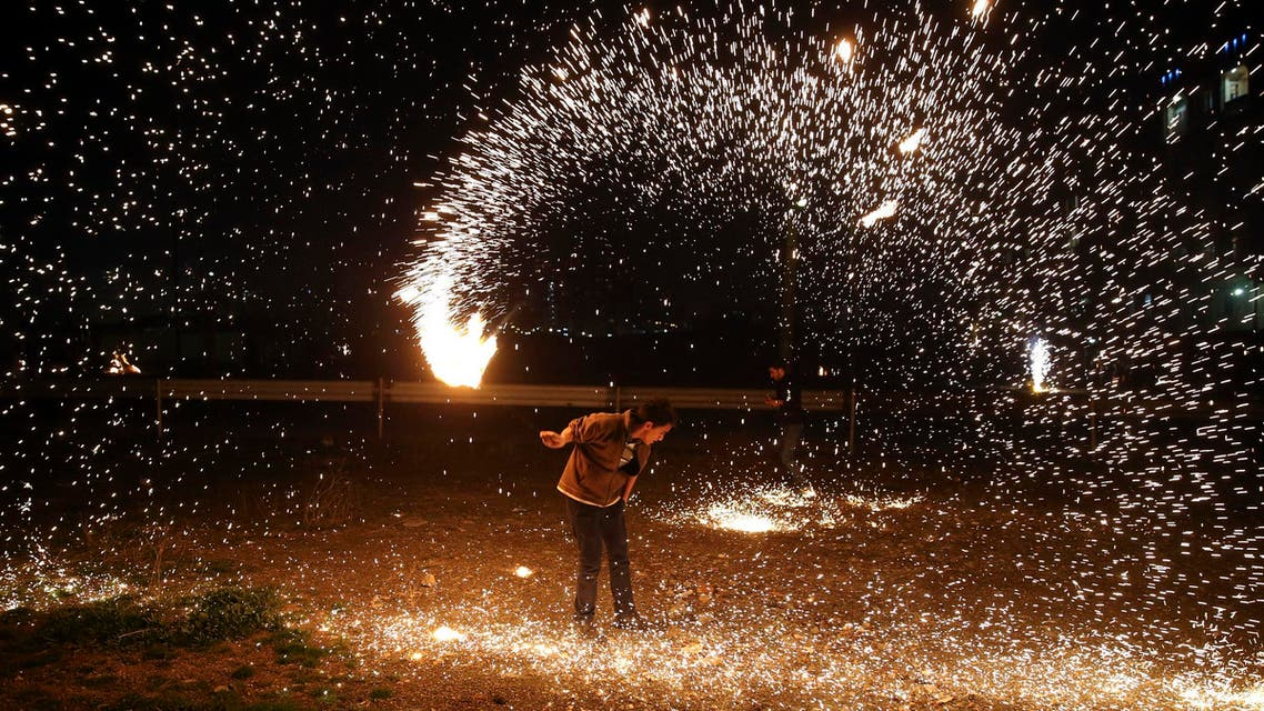 An Iranian man plays with a firework during Chaharshanbe Souri in Tehran on March 17, 2015. (AP)