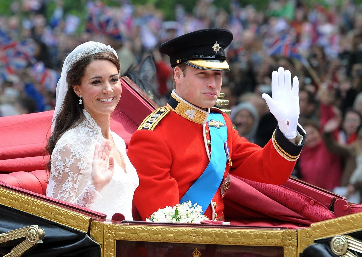 Britain's Prince William and his wife Kate, Duchess of Cambridge, wave as they travel in the 1902 State Landau carriage along the Processional Route to Buckingham Palace, in London, on April 29, 2011. (AFP)