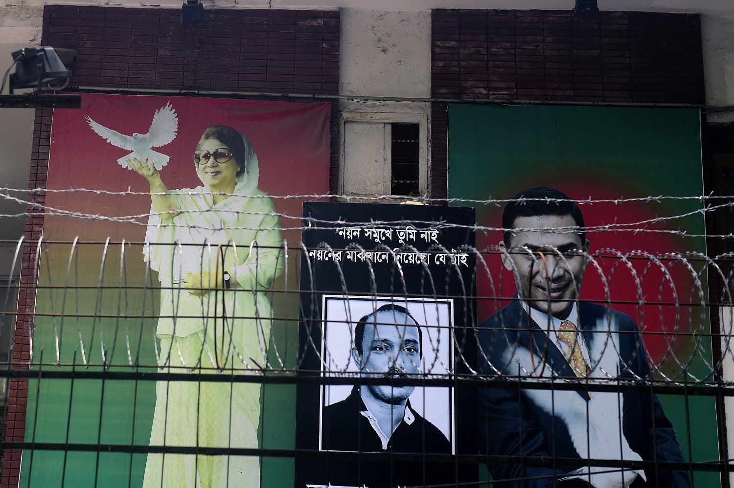 A poster of opposition Bangladesh Nationalist Party (BNP) leader, Khaleda Zia (L) is seen with her two sons late Arafat Rahman Koko (C) and Tarique Rahman (R) in front of BNP office in Dhaka on February 26, 2015. (AFP)