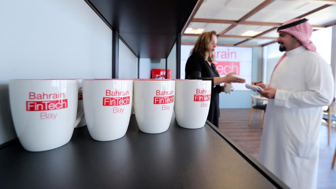 Coffee mugs with logos of Bahrain FinTech Bay on display as staff chat in its office in Bahrain Bay on February 28, 2018. (Reuters)