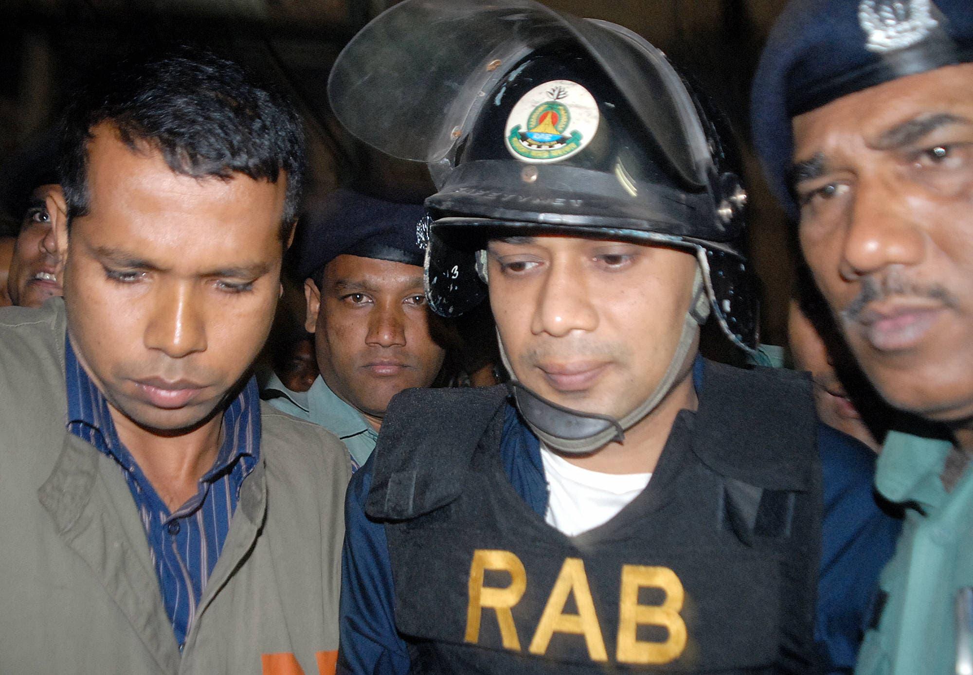 Bangladeshi policemen escort Tarique Rahman to court in Dhaka on 08 March 2007. (AFP)