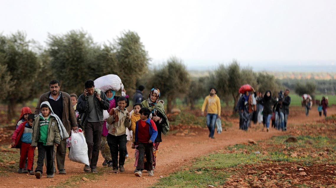 Internally displaced people walk with their belongings in the town of Inab, eastern Afrin, Syria, on March 14, 2018. (Reuters)
