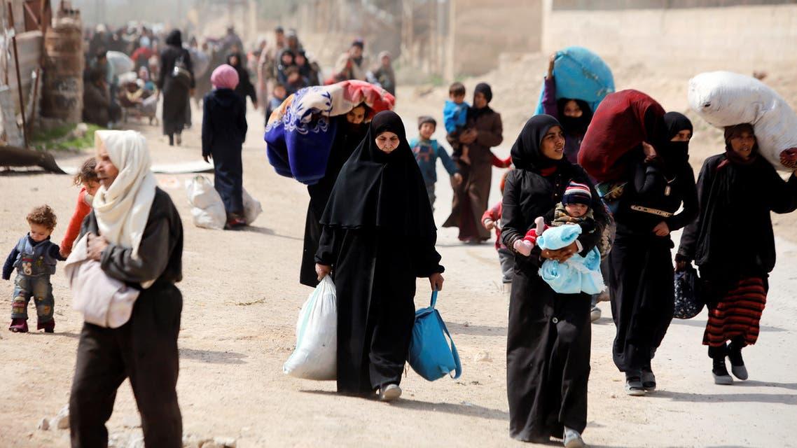 People walk with their belongings as they flee the rebel-held town of Hammouriyeh, in the village of Beit Sawa, eastern Ghouta, Syria March 15, 2018. REUTERS/Omar Sanadiki