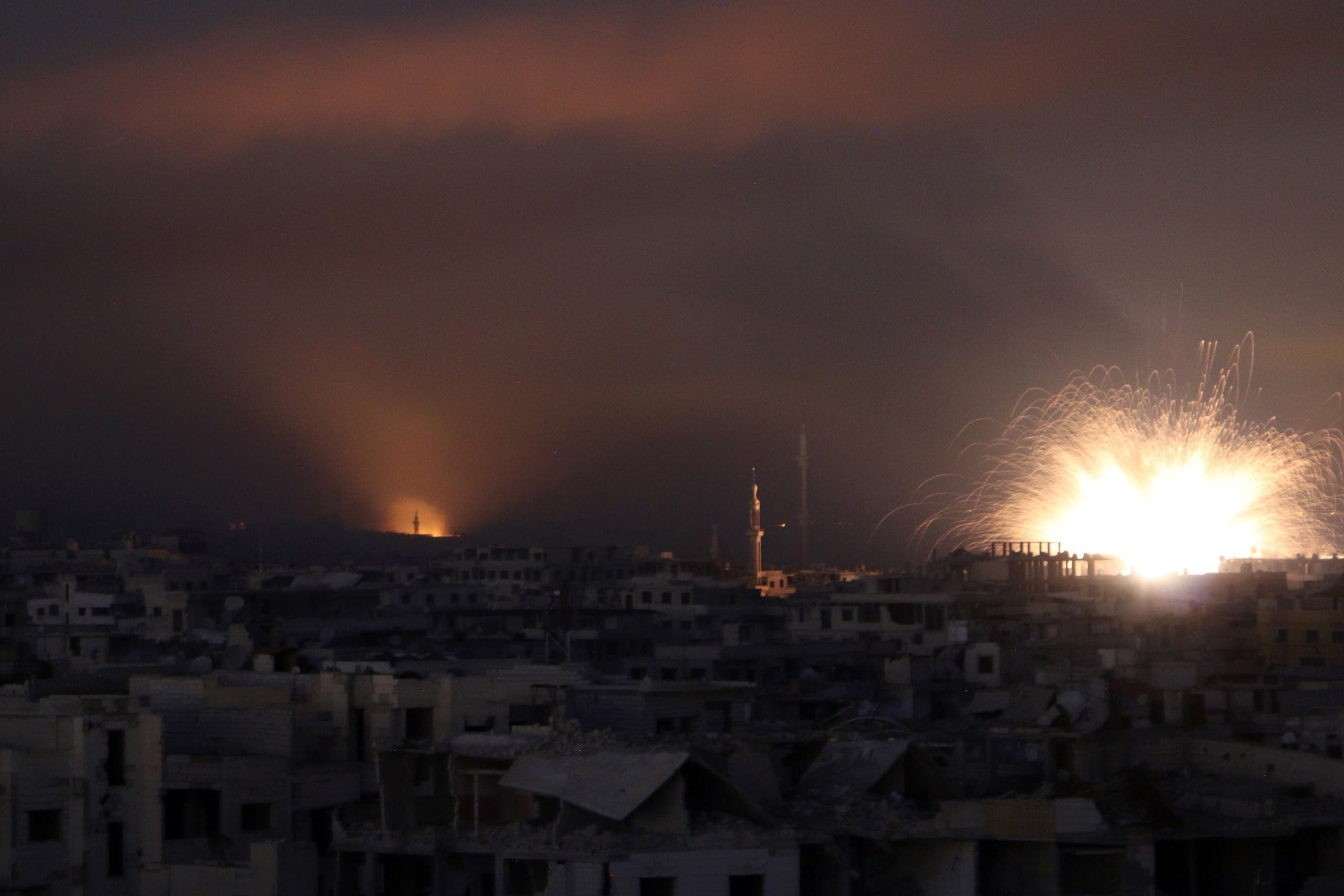 A general view shows explosions lighting the sky following regime air strikes on Zamalka, in the rebel enclave of Eastern Ghouta on the outskirts of Damascus on March 12, 2018. (AFP)