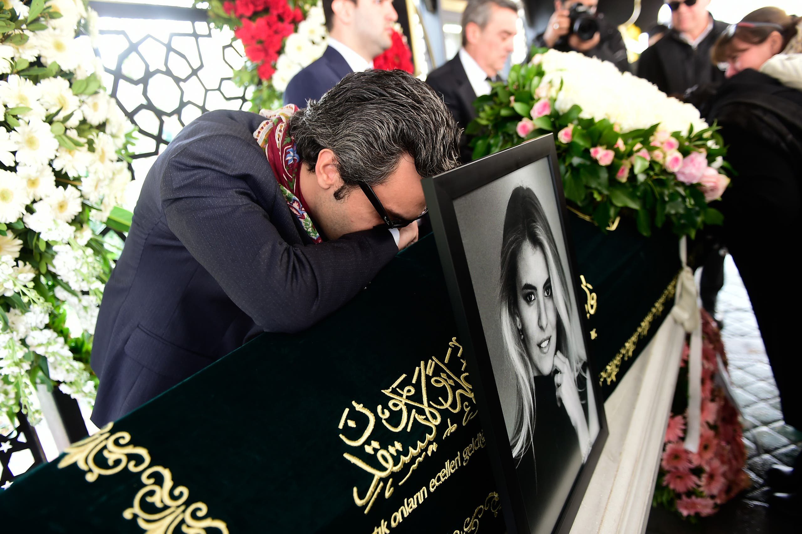 Sinan Urfali (L) husband of Burcu Gundogar Urfali mourns next to his wife's coffin on March 15, 2018 during her funeral cerenomy in Istanbul. Grieving families bade farewell to the young women killed in a plane crash over Iran while returning from a pre-wedding celebration for a Turkish businessman's daughter, in a tragedy that shocked the country. YASIN AKGUL / AFP