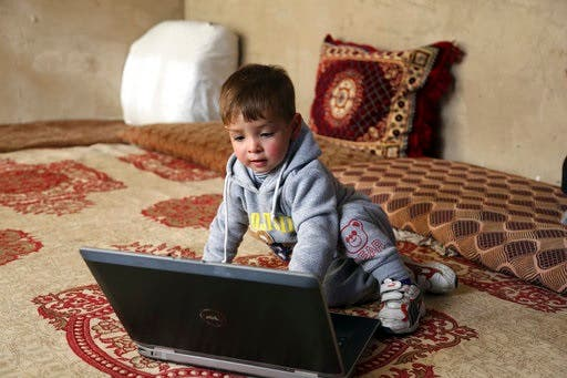 Eighteen-month-old Donald Trump, plays with a computer at his house, in Kabul, Afghanistan, Thursday, March 15, 2018. (AP)