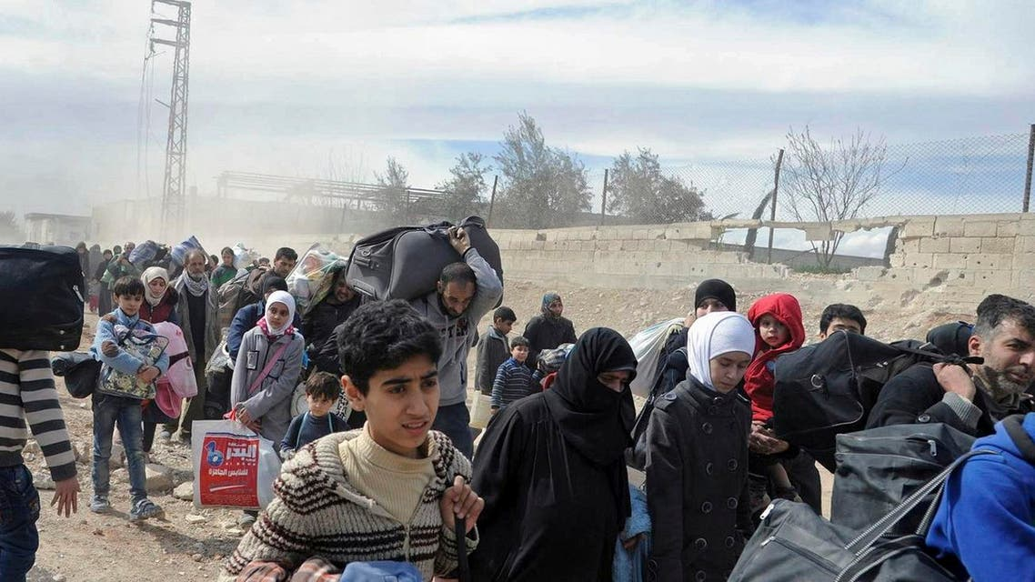 In this photo released by the Syrian official news agency SANA, civilians carry their belongings as they flee from fighting between Syrian government forces and rebels in Hamouria in eastern Ghouta, a suburb of Damascus, on March. 15, 2018.  (AP)