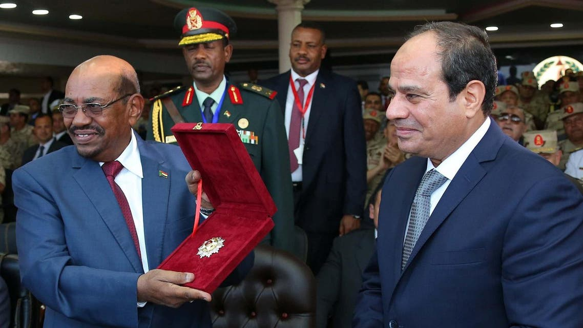 """A handout picture made available on October 5, 2016 by the Egyptian presidency shows Egyptian President Abdel Fattah al-Sisi (R) awarding his Sudanese counterpart Omar al-Bashir (L) the """"Sinai Star"""". (AFP)"""