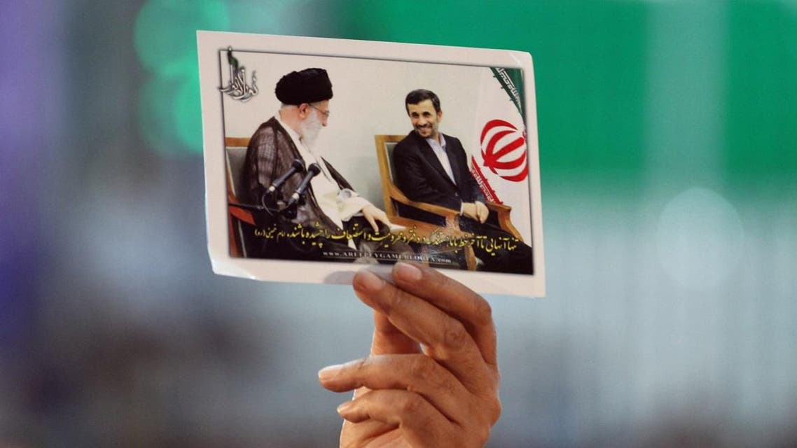 An Iranian man holds portraits of President Mahmoud Ahmadinejad (R) and supreme leader, Ayatollah Ali Khamenei. (File photo: AFP)