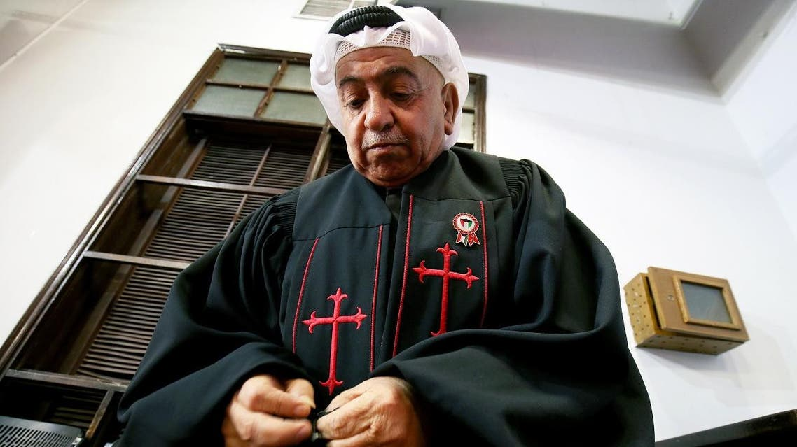 Father Emmanuel Benjamin Jacob Gharib, Chairman of the National Evangelical Church of Kuwait and Pastor of the Kuwaiti Presbyterian Church, adjust his clerical robe at the National Evangelical Church in Kuwait City on February 20, 2018. (AFP)
