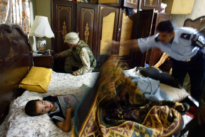 A U.S. soldier and Iraqi policeman search a room as an Iraqi child sleeps on the bed during a joint raid. (Reuters)