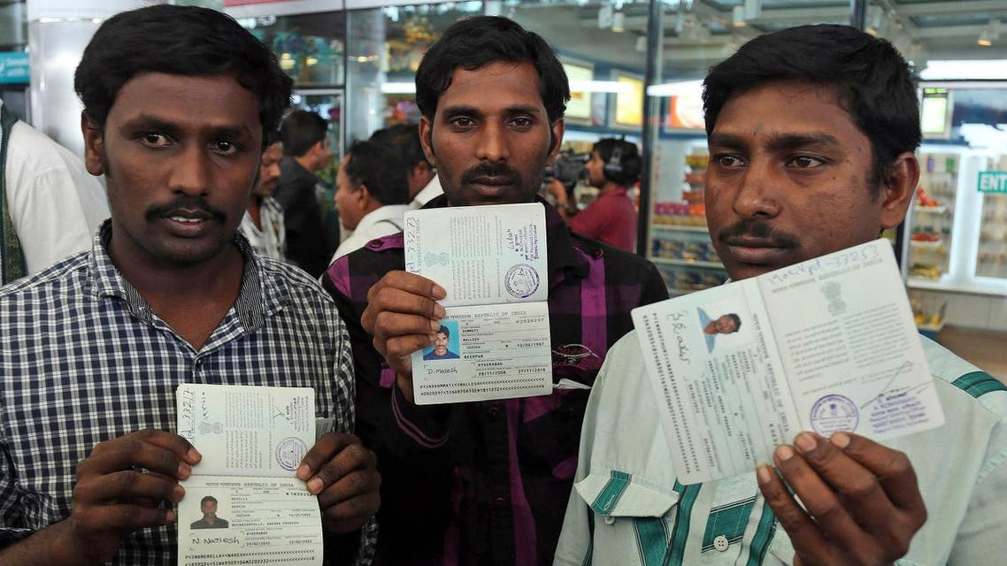Indian workers from Iraq display their passports to the media upon arrival at the airport in Hyderabad, India, Saturday, July 5, 2014. (AP)