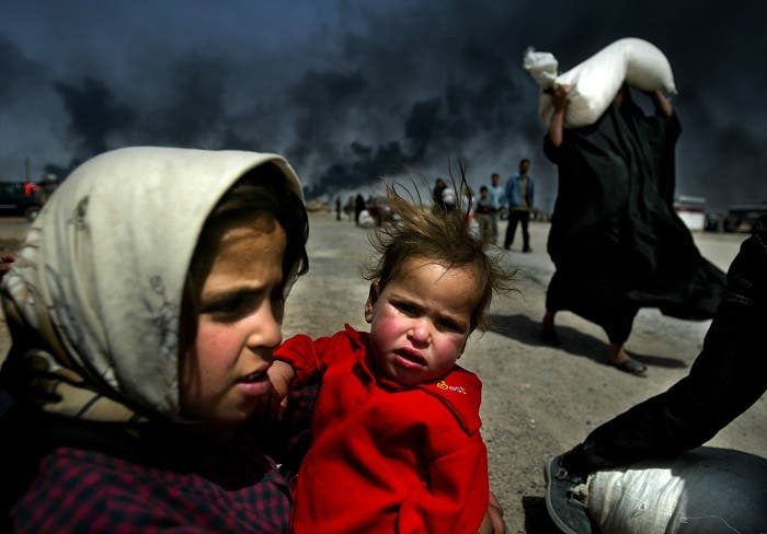An Iraqi girl holds her sister as she waits for her mother (R) to bring over food bought in Basra, March 29, 2003. (Reuters)