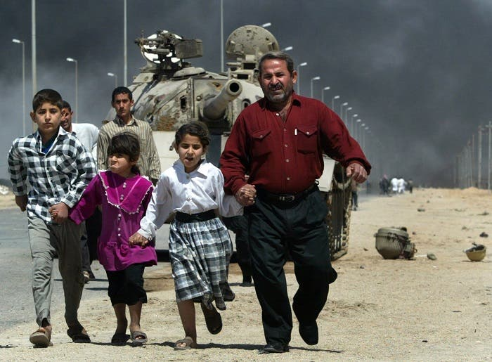 A family flees past a destroyed Iraqi T-55 tank after a mortar attack on British Army positions in the southern city of Basra, March 28, 2003. (Reuters)